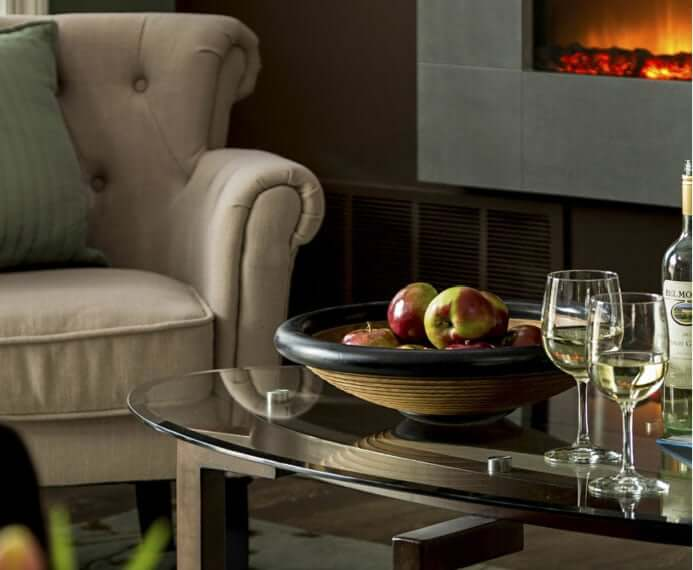 comfy chair in front of table with wine and fruit