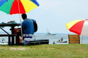 man sitting at a picnic table under a rainbow umbrella, playing the guitar overlooking Rock Hall Beach with boats on the horizon