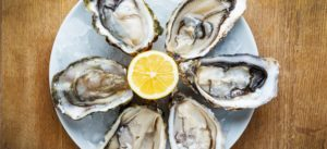 Fresh oysters in a white plate with ice and lemon on a wooden desk