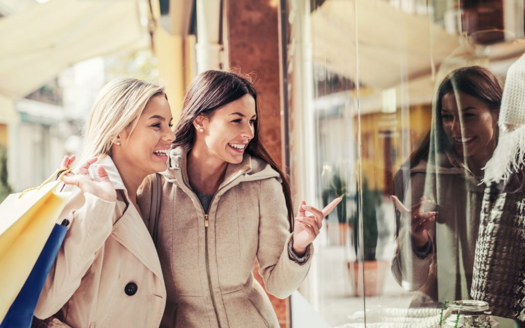Women in shopping. Two happy women with shopping bags enjoying in shopping, having fun in the city. Consumerism, shopping, lifestyle concept